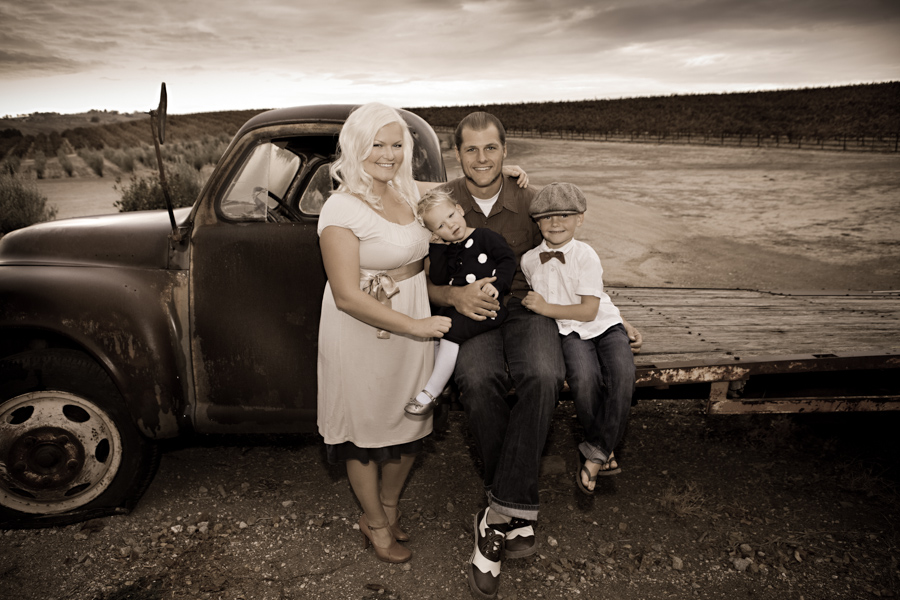 family in vineyard on old truck