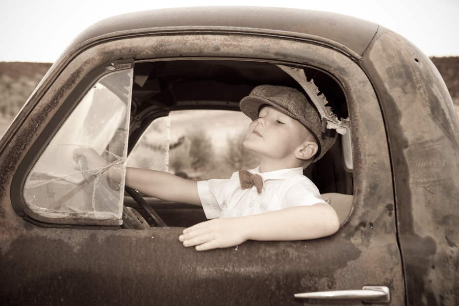 little boy in old truck with bow tie and hat